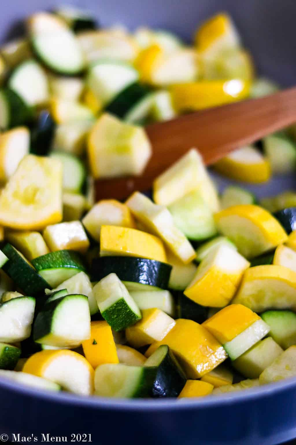 A side shot of a pan of sauteeing yellow and zucchini squash