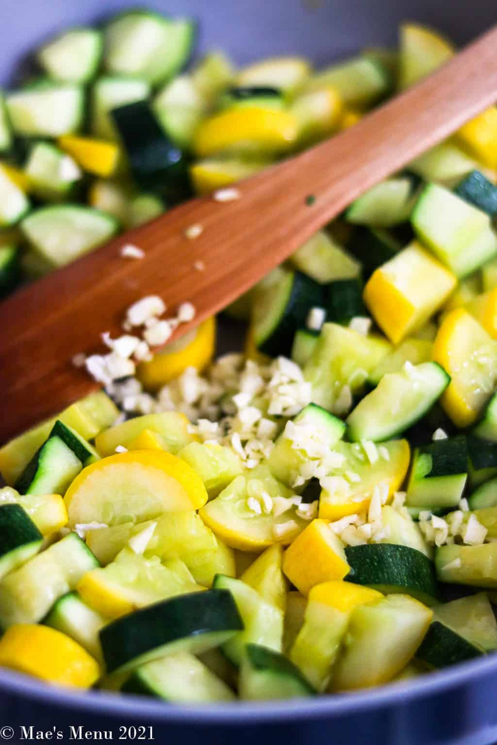 An up-close shot of yellow squash and zucchini with garlic in a saute pan