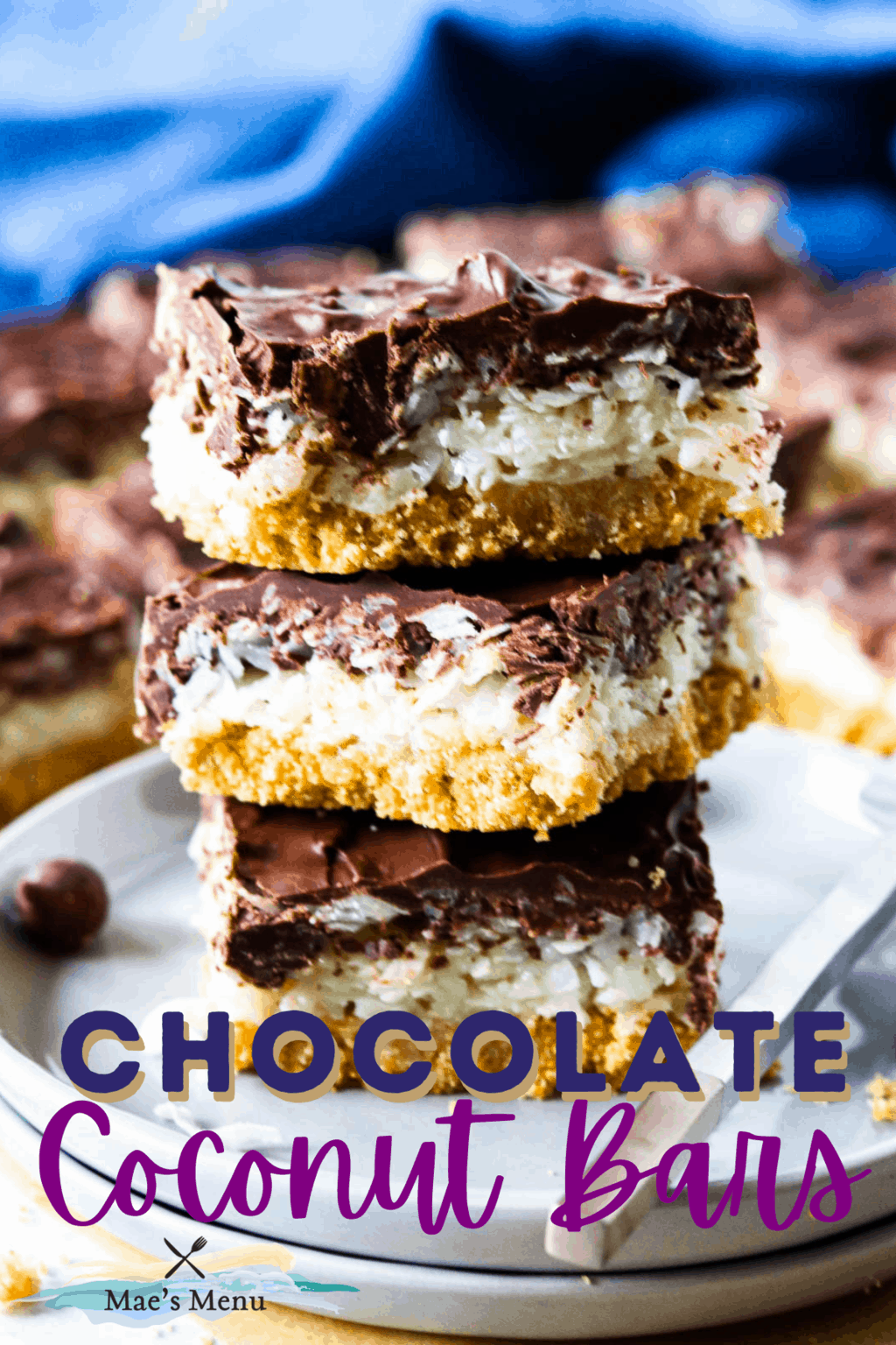 A pinterest pin for chocolate coconut bars with an upclose shot of the bars on a stack of blue plates
