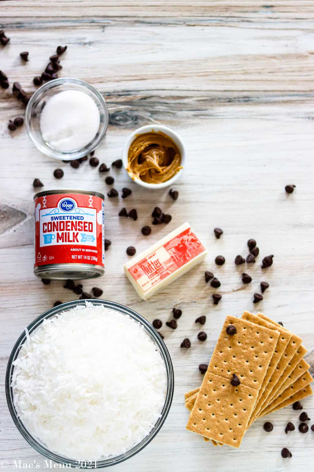 All the ingredients for chocolate coconut bars: sweetened condensed milk, sugar, peanut butter, butter, chocolate chips, shredded coconut, and graham crackers