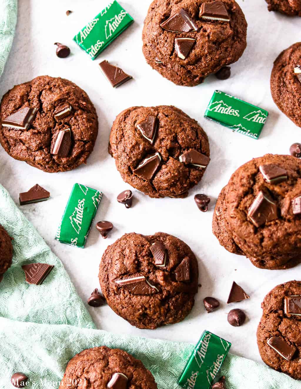 Mint chocolate chip cookies scattered on the counter with chocolate and mints