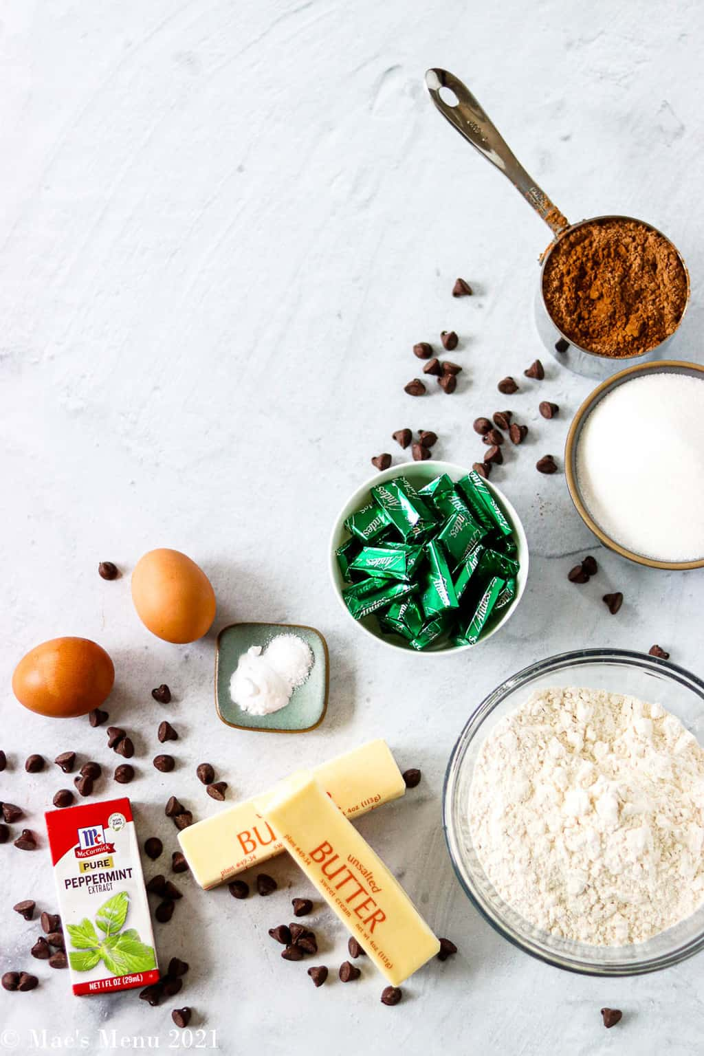 All the ingredients for andes chocolate mind cookies: andes mints, flour, sugar, cocoa, baking soda and salt, butter, pure peppermint extract, eggs, and chocolate chips