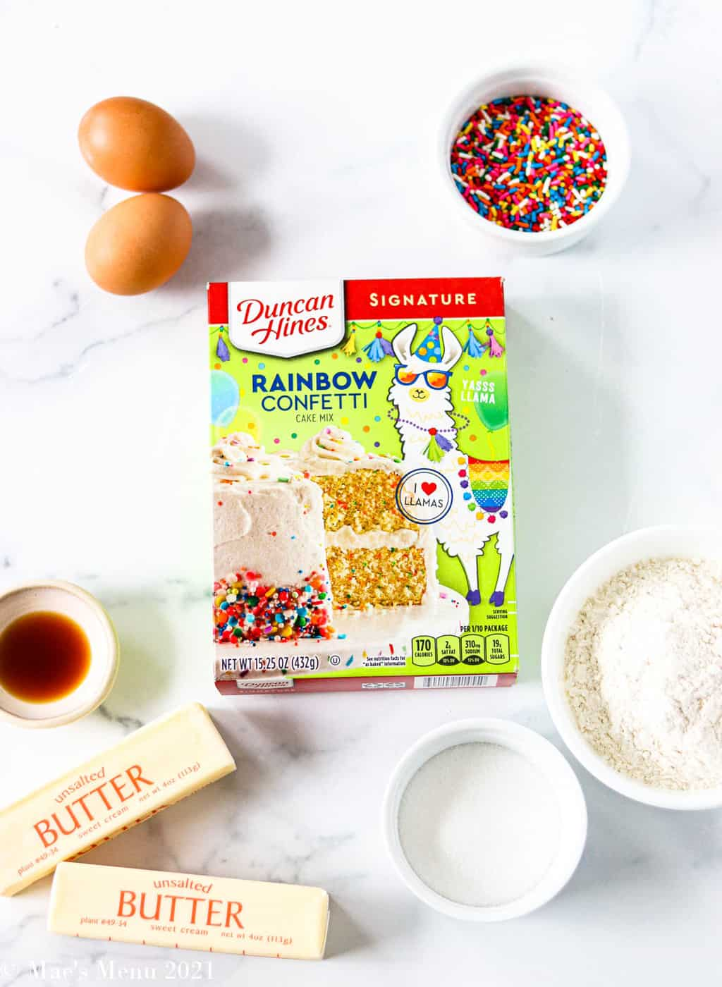 All the ingredients for rainbow confetti -- confetti cake mix, sprinkles, eggs, vanilla extract, butter, sugar, and flour