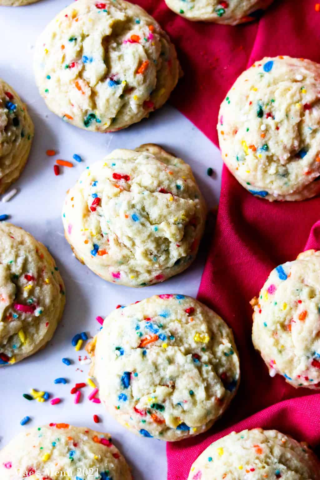 An up-close shot of funfetti cookies on a counter and pink towel with sprinkles between them