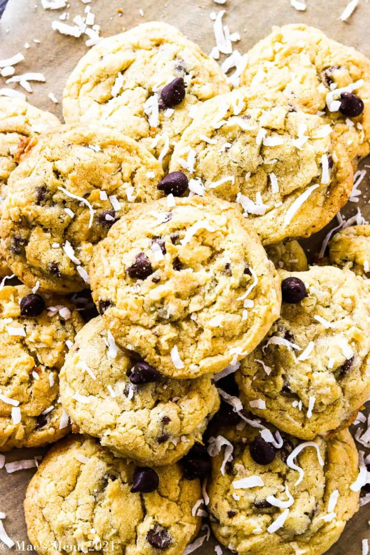 a pile of chocolate chip coconut cookies on a wooden table