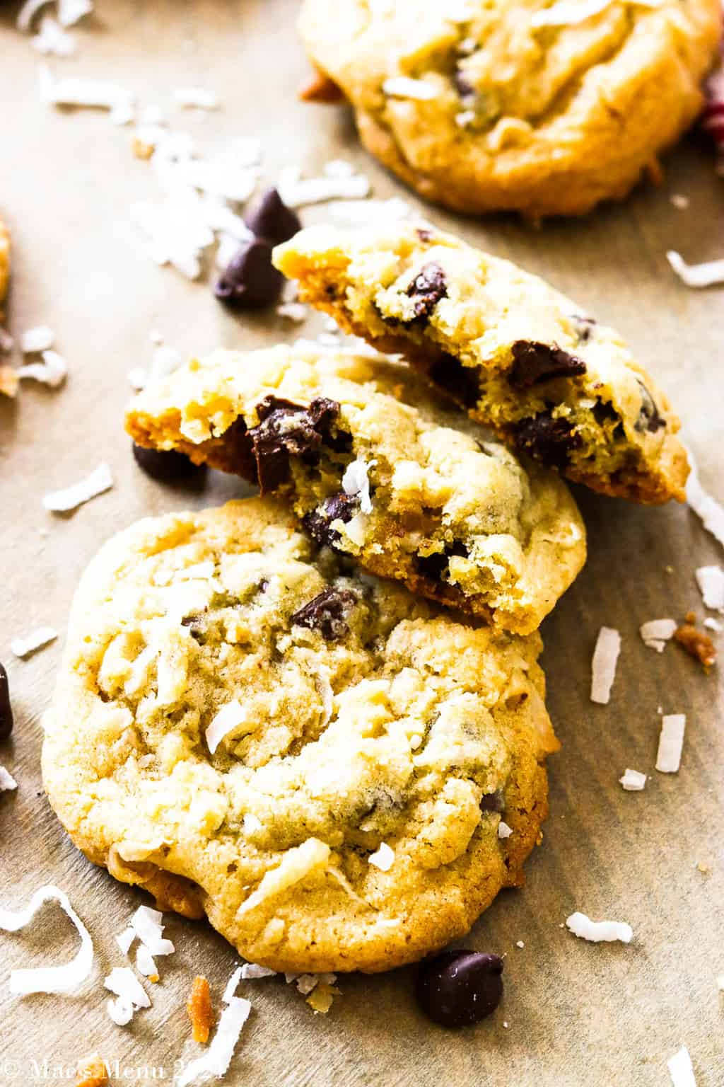 A side shot of chocolate chip and coconut cookies with a split open cookie on top