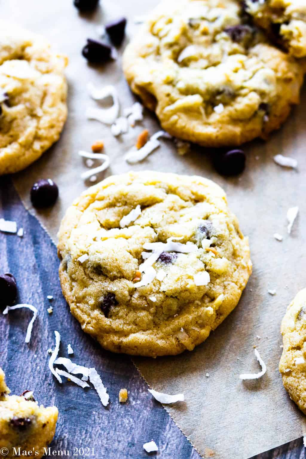 An overhead shot of coconut chocolate chip cookies on a counter with coconut and chocolate chips