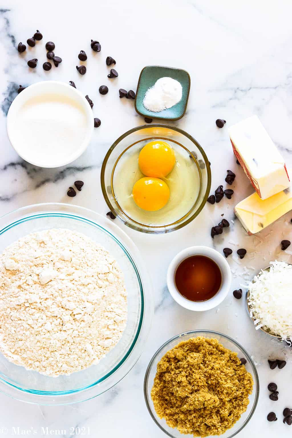 All o the ingredients for chocolate chip coconut cookies: flour, sugar, eggs, baking soda and salt, butter, vanilla extract, flaked coconut, and brown sugar