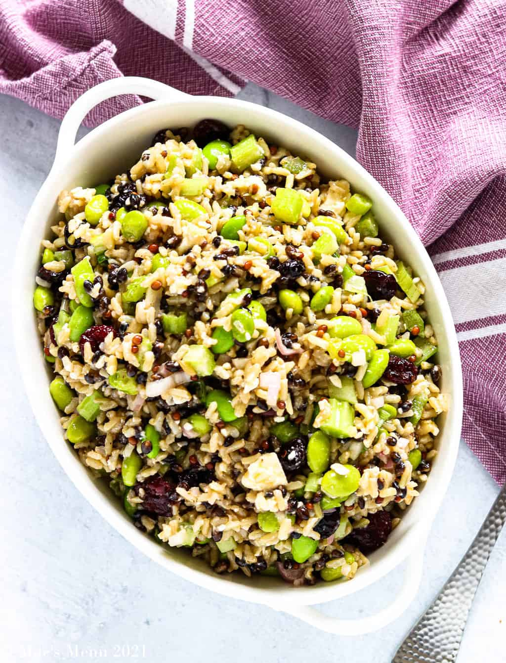 An overhead shot of a small serving dish of cranberry & edamame brown rice salad