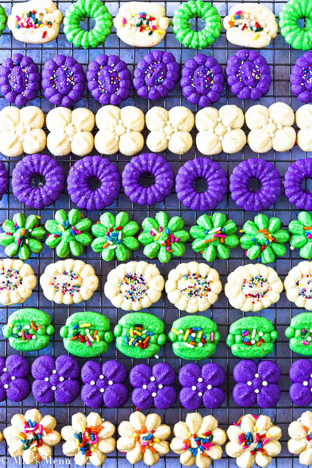 A large cooling rack full of green, purple, and vanilla cream cheese spritz cookies
