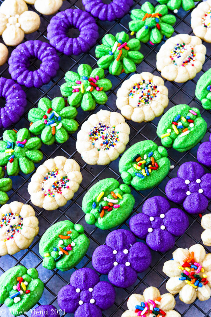 Purple, green, and white cream cheese spritz cookies on a cooking rack