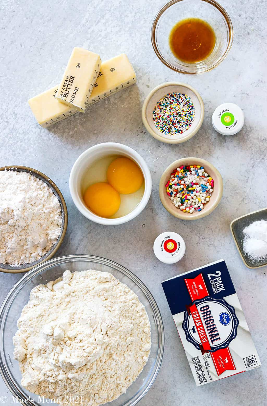 All the ingredients for cream cheese spritz cookies: flour, powdered sugar, egg yolks, cream cheese, sprinkles, butter, vanilla, salt, baking soda, and gel food coloring
