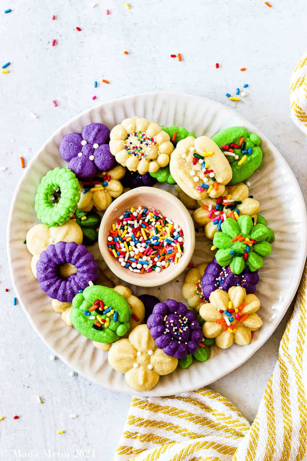 A plate of cream cheese spritz cookies on a white plate with a small dish of sprinkles