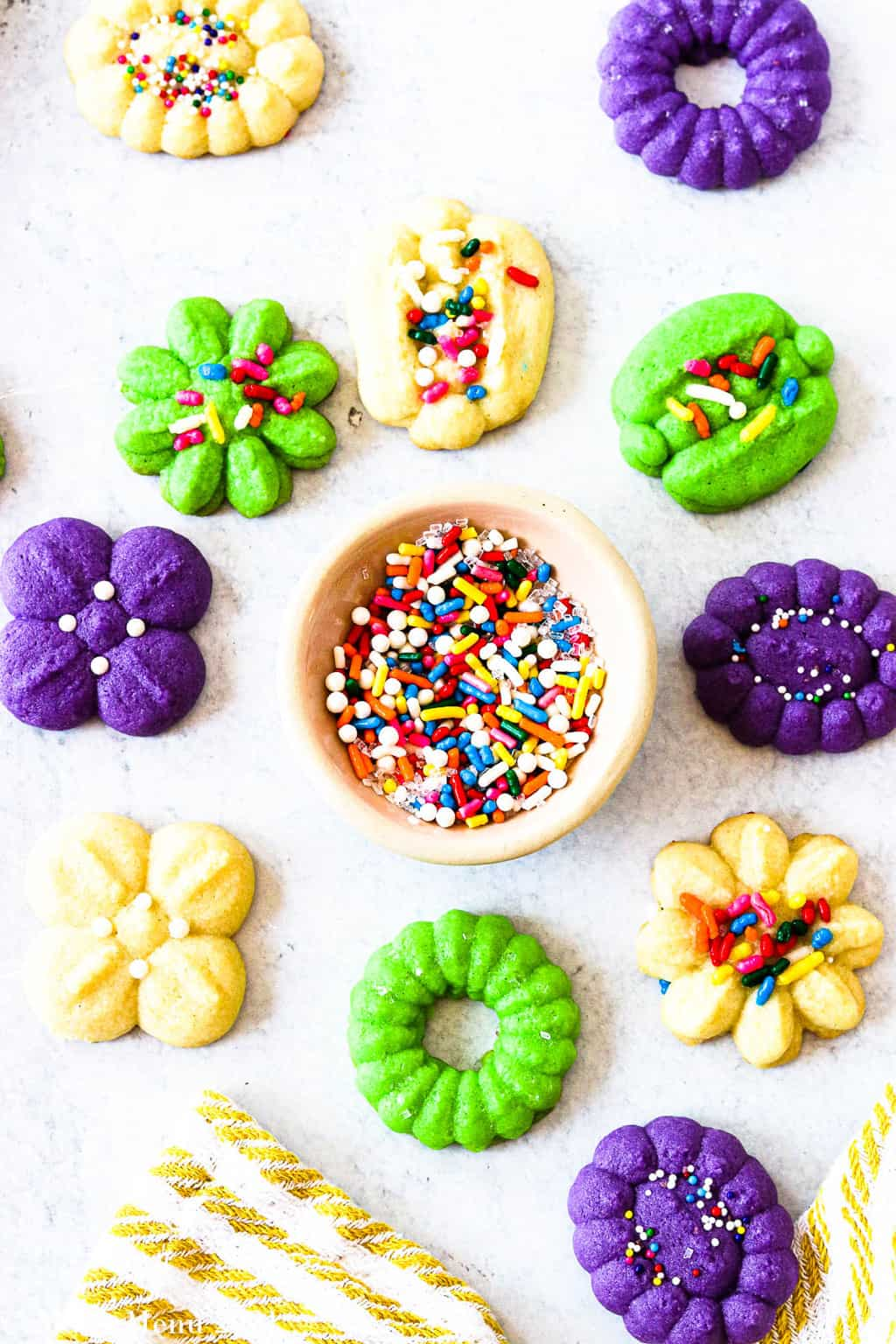 Some cream cheese spritz cookies spread out around a small dish of sprinkles