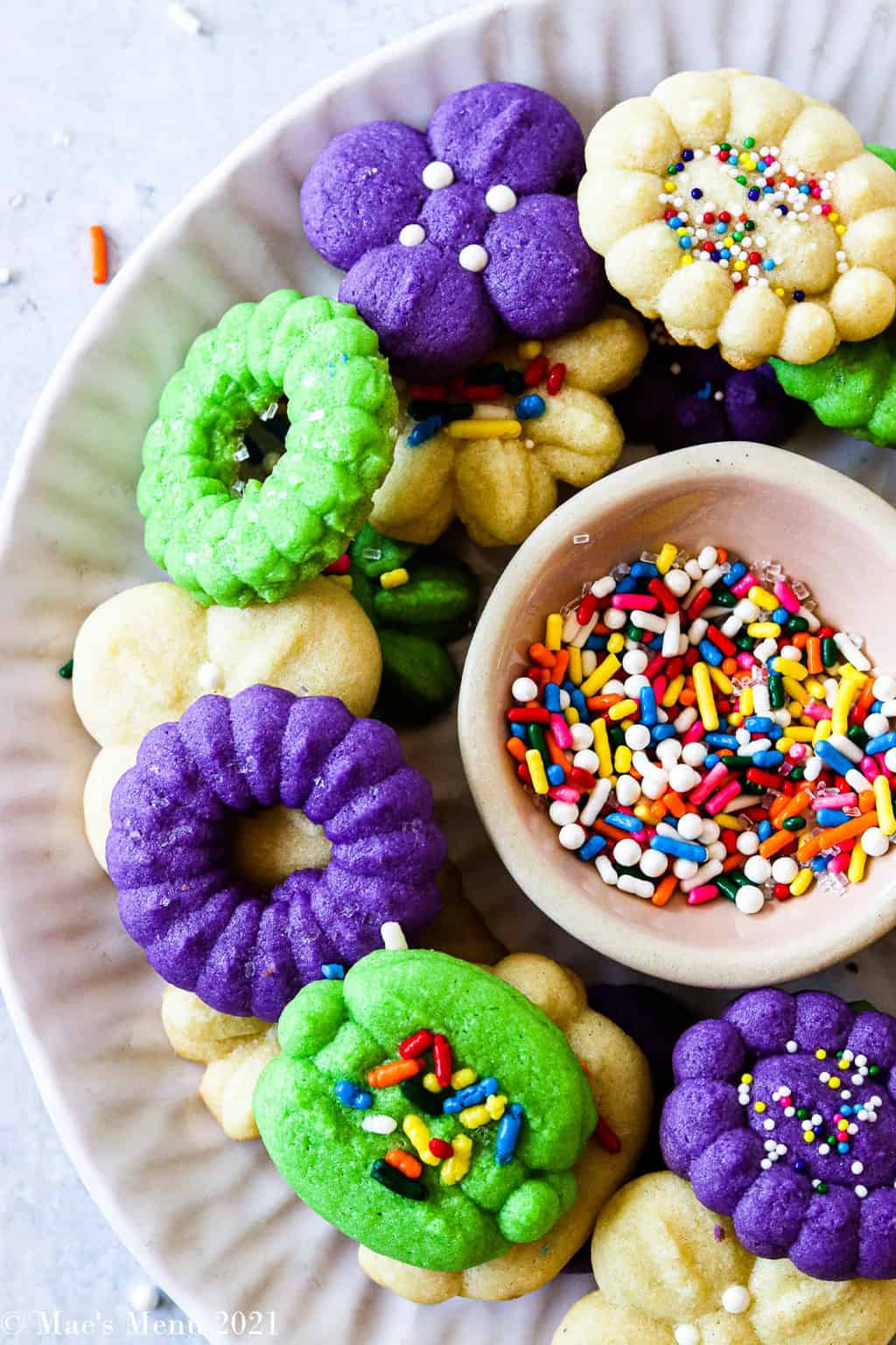 A side shot of a plate of cream cheese spritz cookies surrounding a small dish of sprinkles