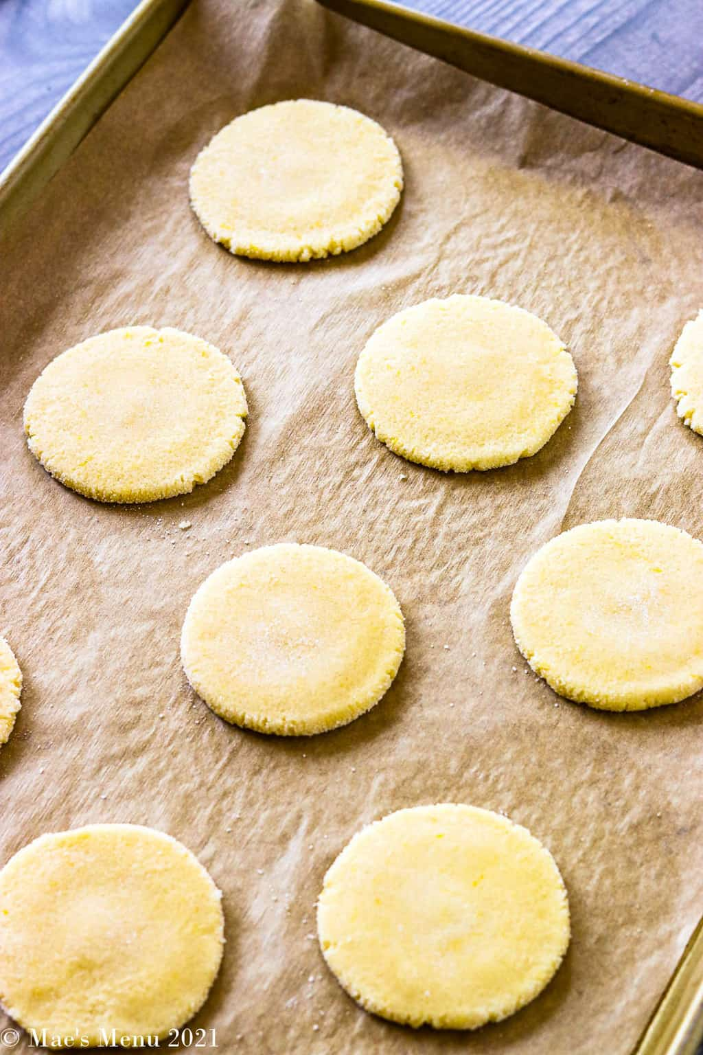 Flattened rounds of cookie dough on a parchment paper lined baking sheet