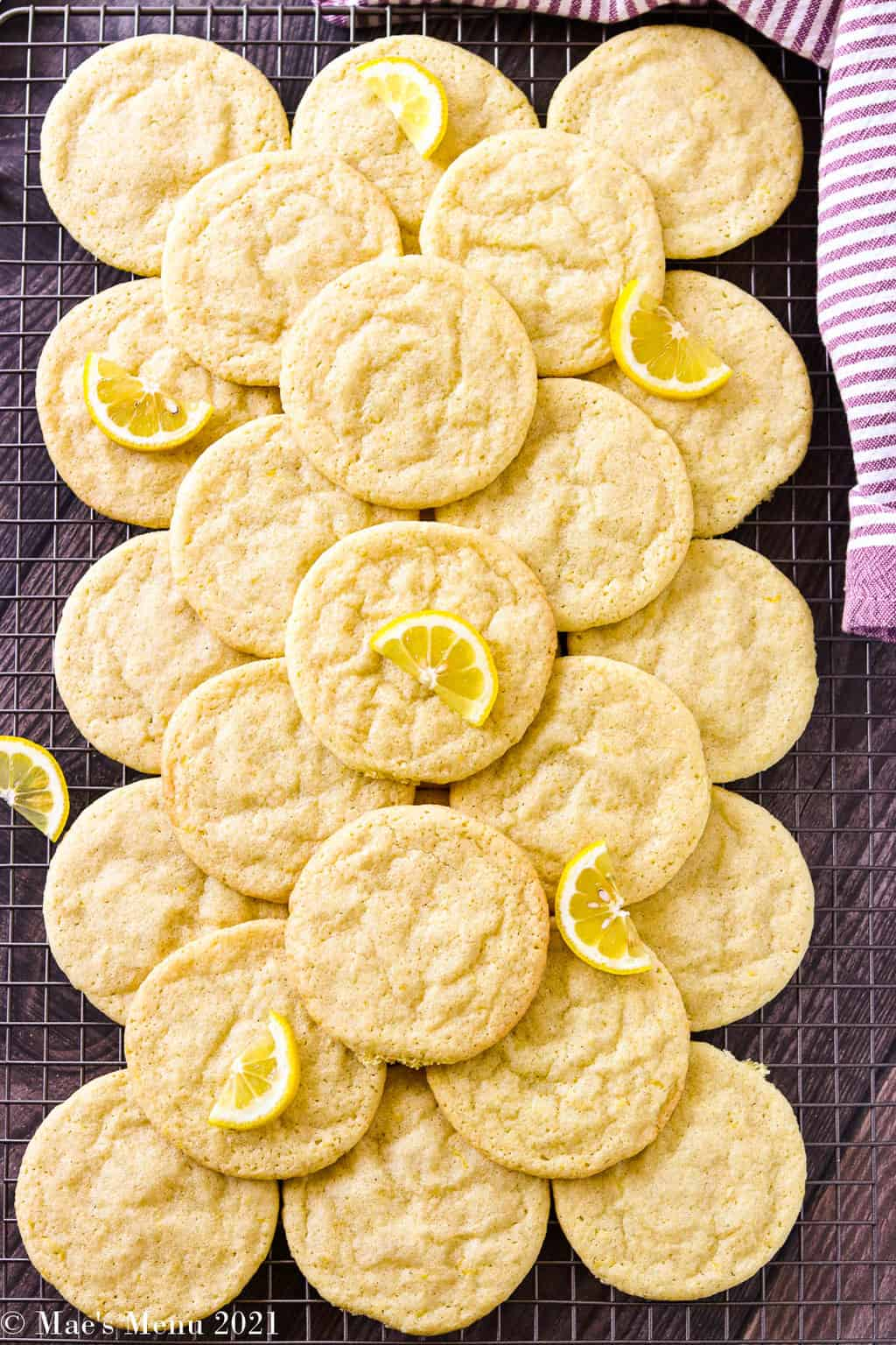 Lemon sugar cookies stacked on a wire cooling rack with lemon wedges