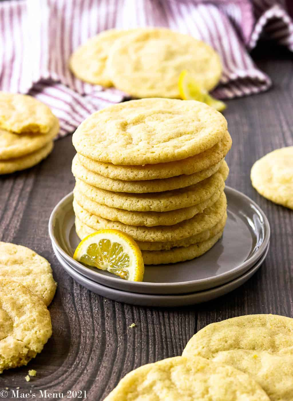 A stack of lemon sugar cookies on a grey plate with other sugar cookies all around