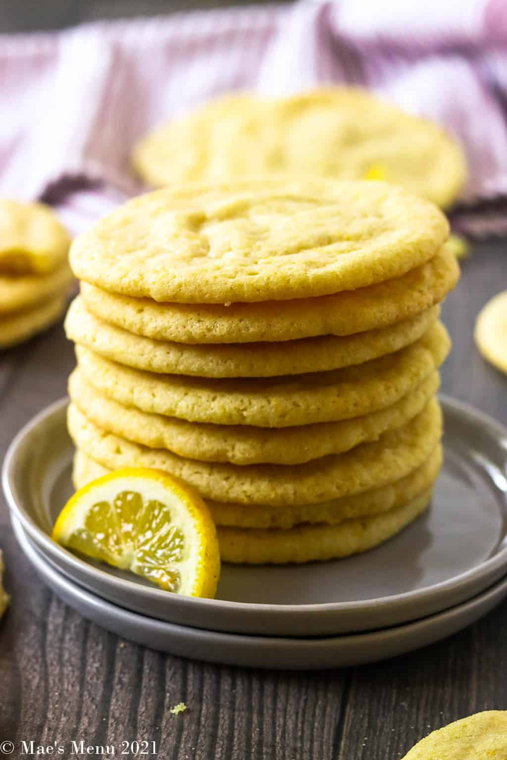 An up-close shot of a stack of lemon sugar cookies on grey plates