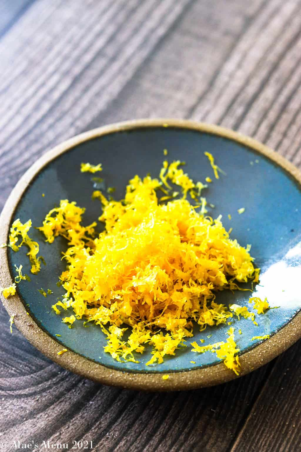 A side shot of a small dish of lemon zest