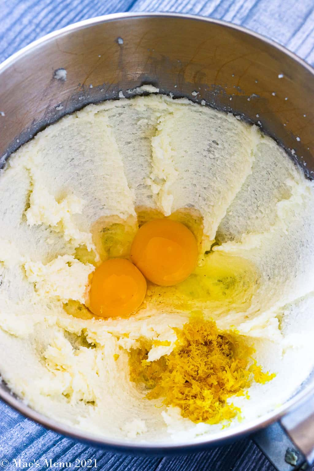 A mizing bowl of creamed butter and sugar with an egg, egg yolk, and lemon zest