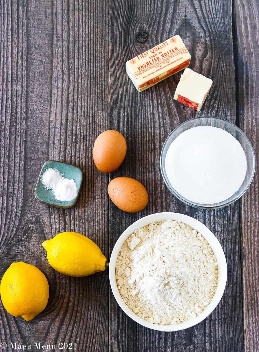 All of the ingredients for lemon sugar cookies: all purpose flour, lemons, eggs, baking soda, salt, sugar, and butter