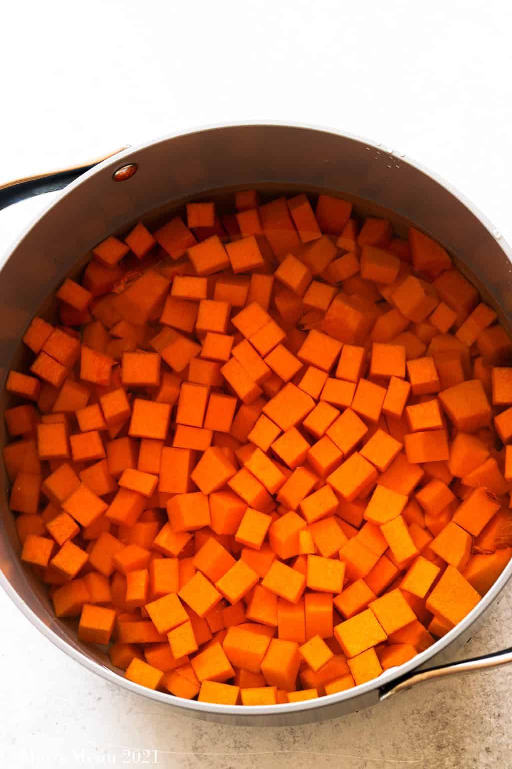 An overhead shot of a pot of cubed butternut squash in water