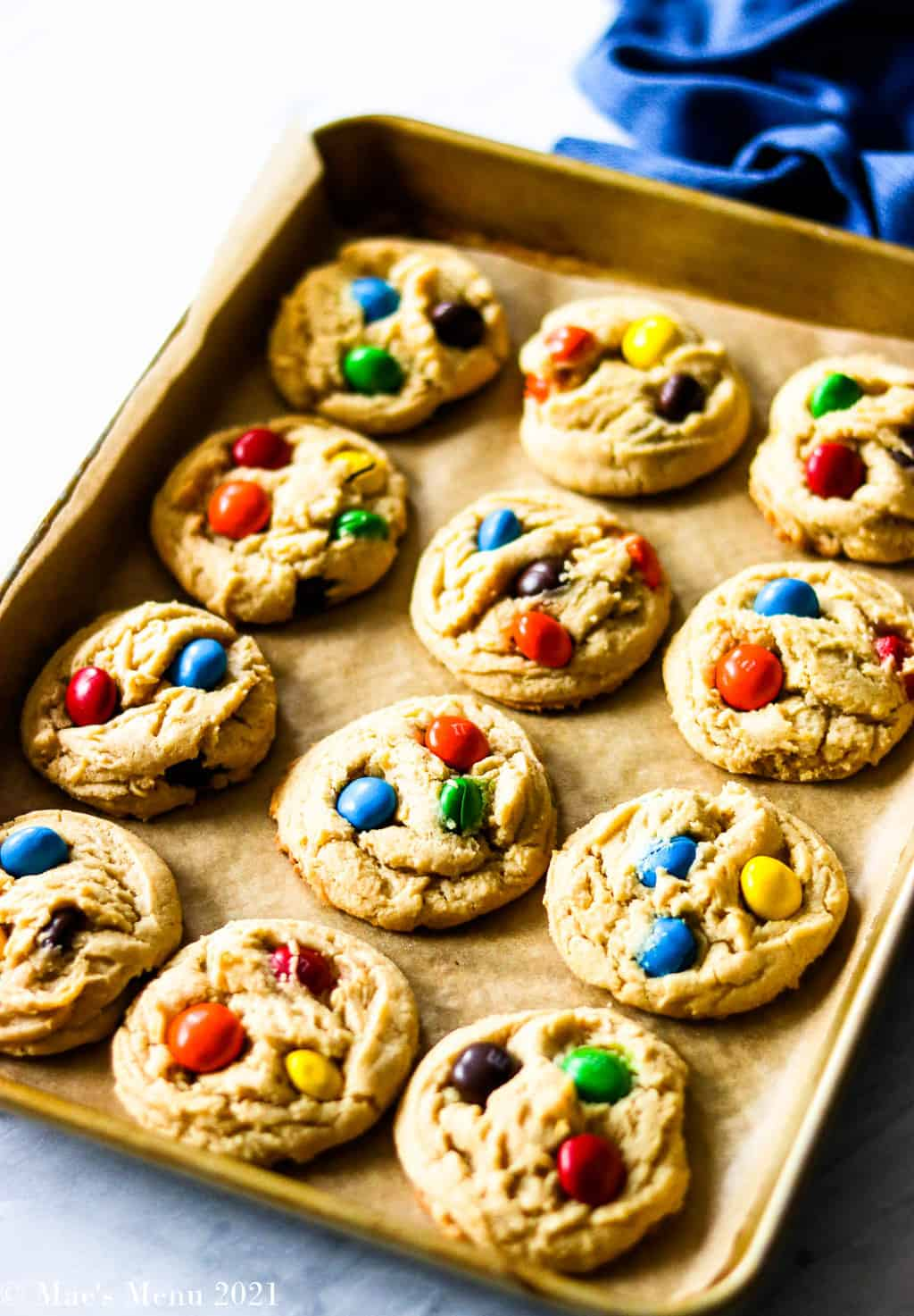 A tray of peanut butter M&M cookies with a blue towel in the background