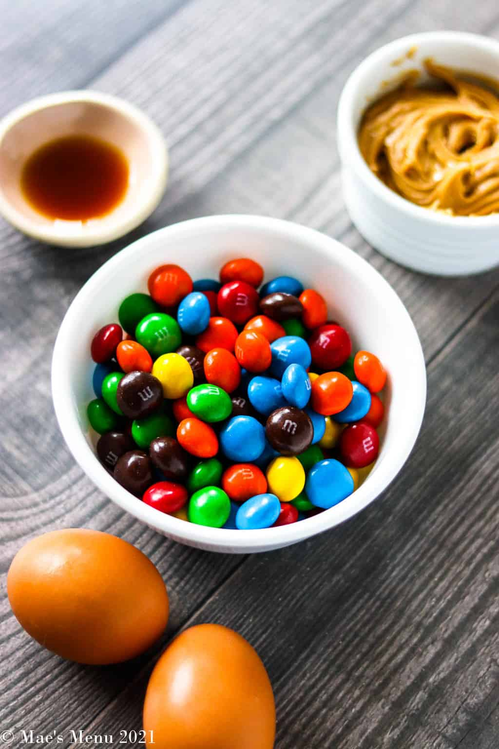 A dish of peanut butter M&Ms, eggs, peanut butter, and vanilla extract