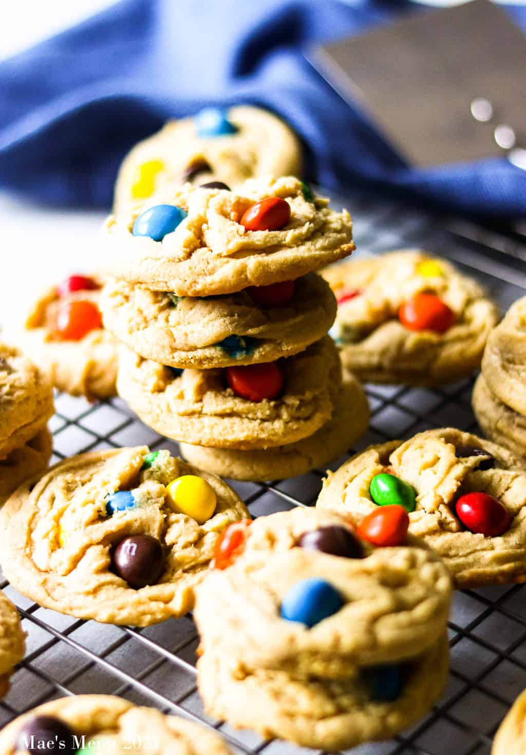A stack of peanut butter M&M cookies on a cooling sheet with a blue towel in the background