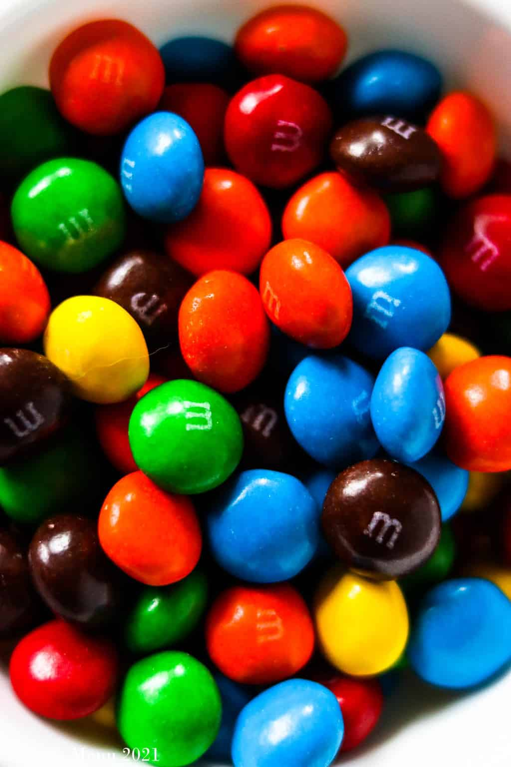 An up-close shot of a dish of peanut butter M&Ms