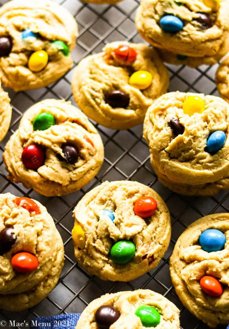 An up close overhead shot of piles of peanut butter M&M cookies on a cooling rack