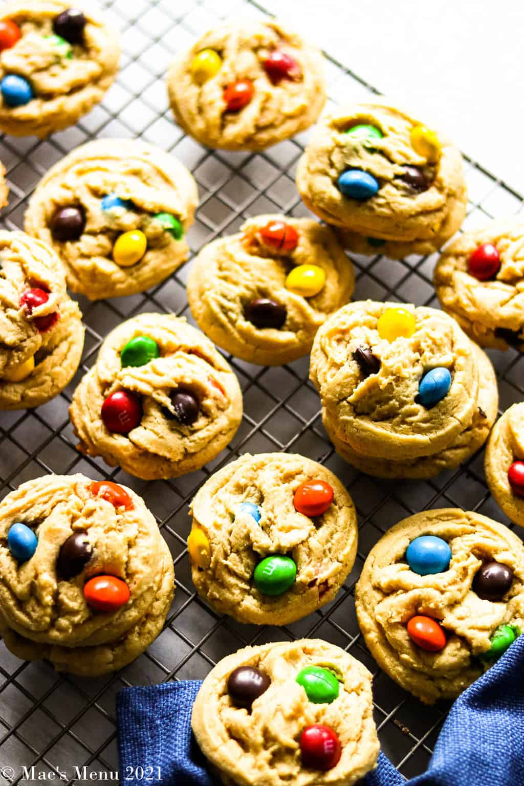 Peanut butter M&M cookies on a cooling rack with a blue towel