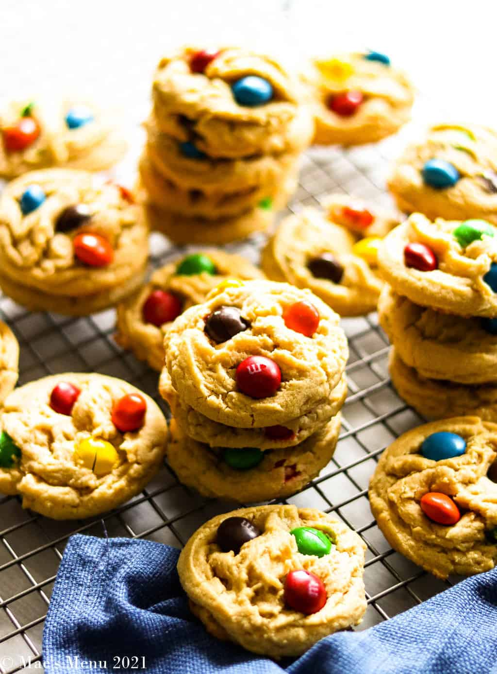 stacks of Peanut butter M&M cookies on a cooling rack by a blue towel