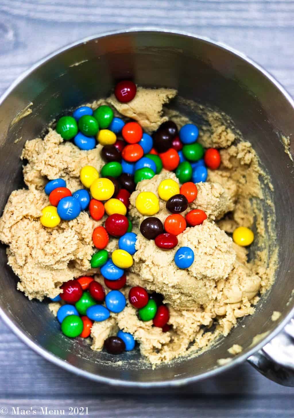 Adding peanut butter M&Ms to the bowl with the peanut butter mixing bowl