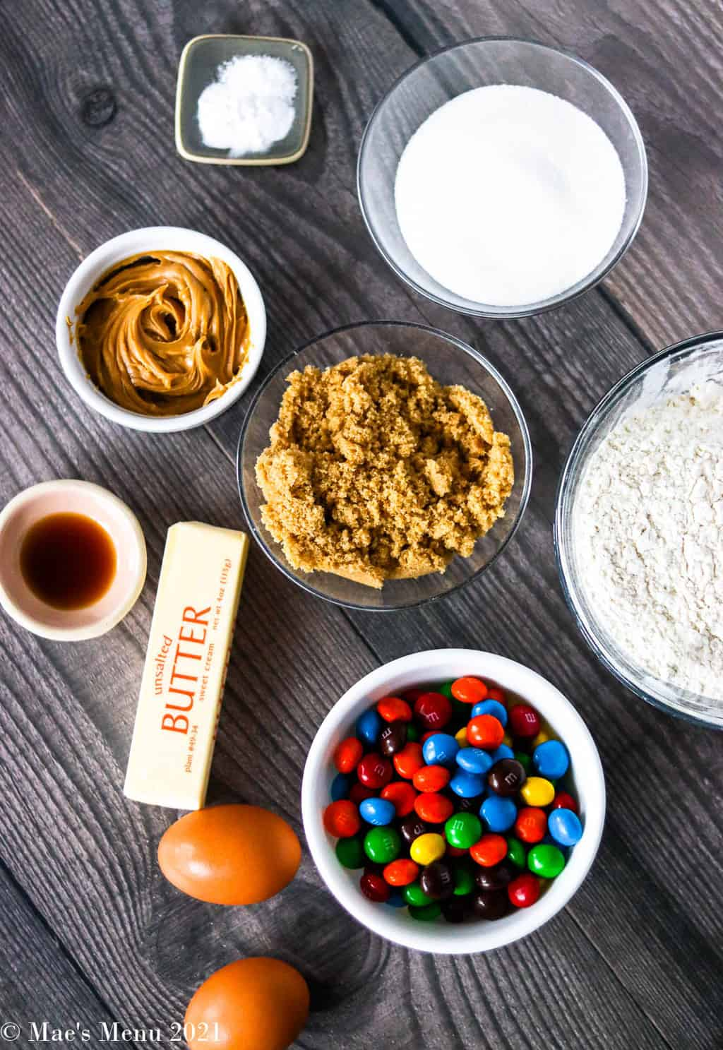 All the ingredients for peanut butter M&M cookies: peanut butter M&Ms, brown sugar, sugar, flour, eggs, butter, vanilla extract, peanut butter, baking soda, and salt