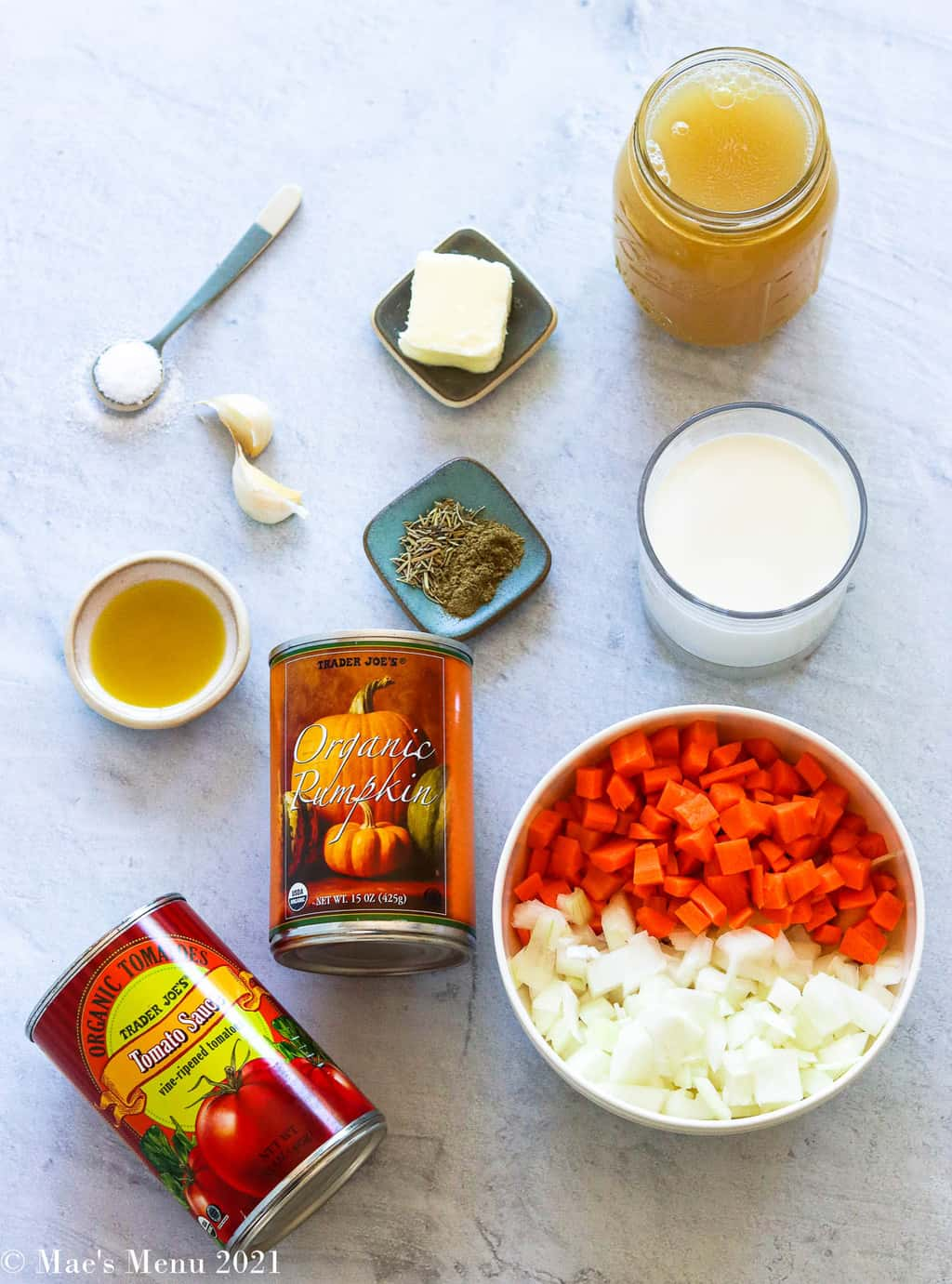 All of the ingredients for pumpkin pasta sauce: chicken broth, butter, seasonings, salt, garlic, half & half, olive oil, pumpkin puree, tomato sauce, carrots, and onions