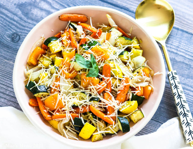 A horizontal shot of a peach colored bowl of air fryer veggies with a gold serving spoon next to it