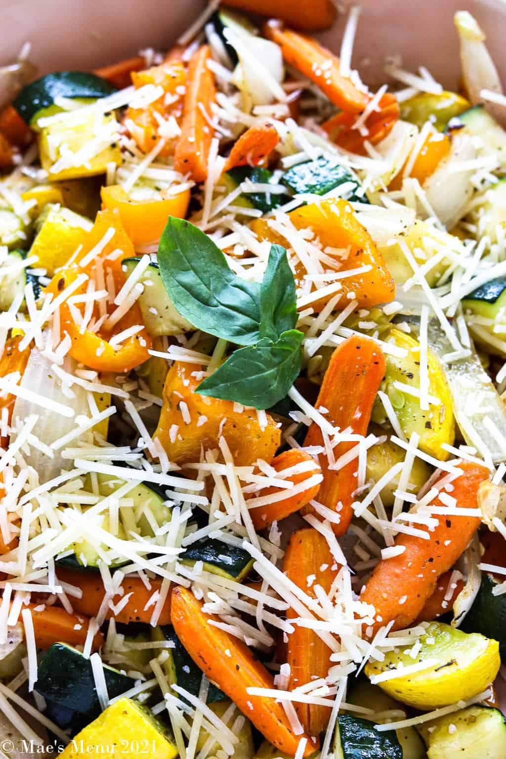 An up-close shot of a bowl of air fryer veggies covered with parmesan cheese