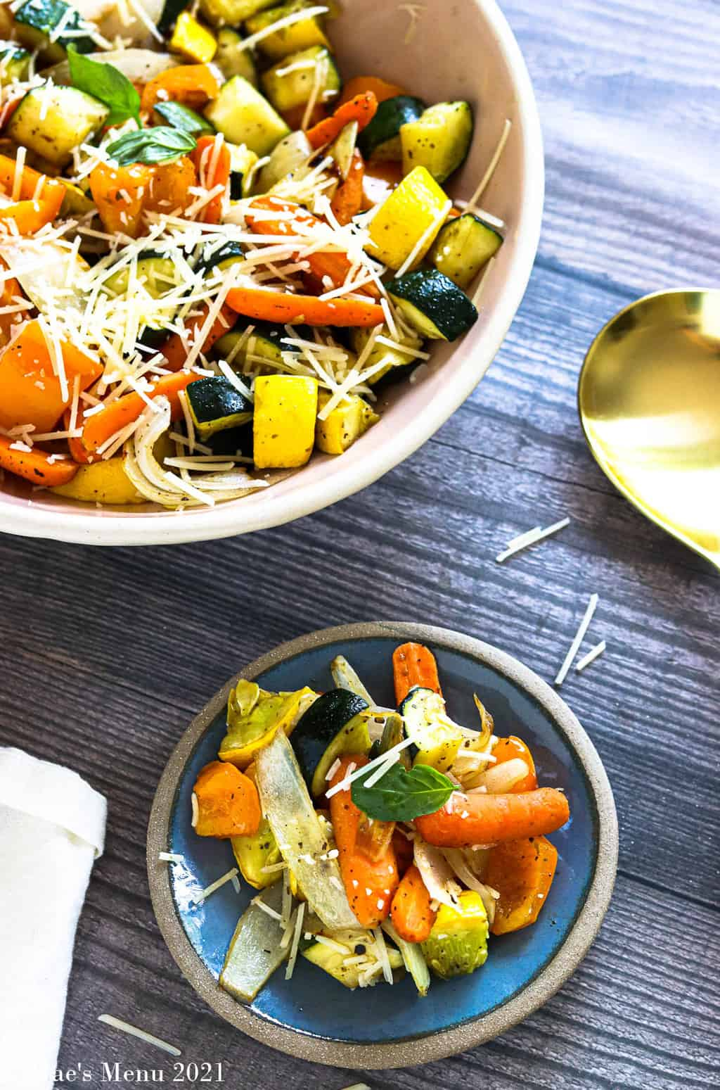 A small dish of air fryer veggies next to a large serving bow of them