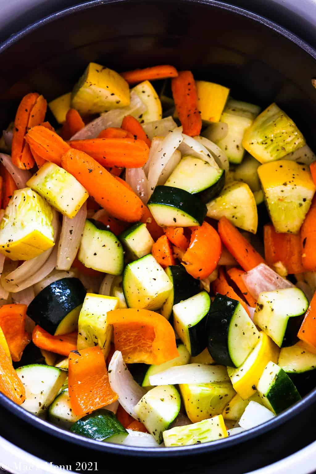 An overhead shot of an air fryer basket with veggies coated in oil and spices