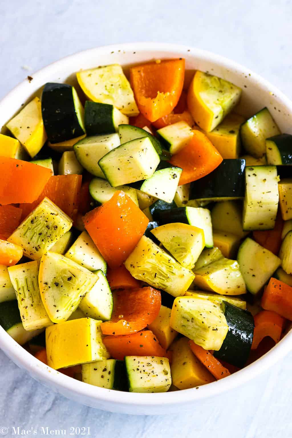An overhead shot of a large white mixing bowl with squash and peppers coated in olive oil and seasonings