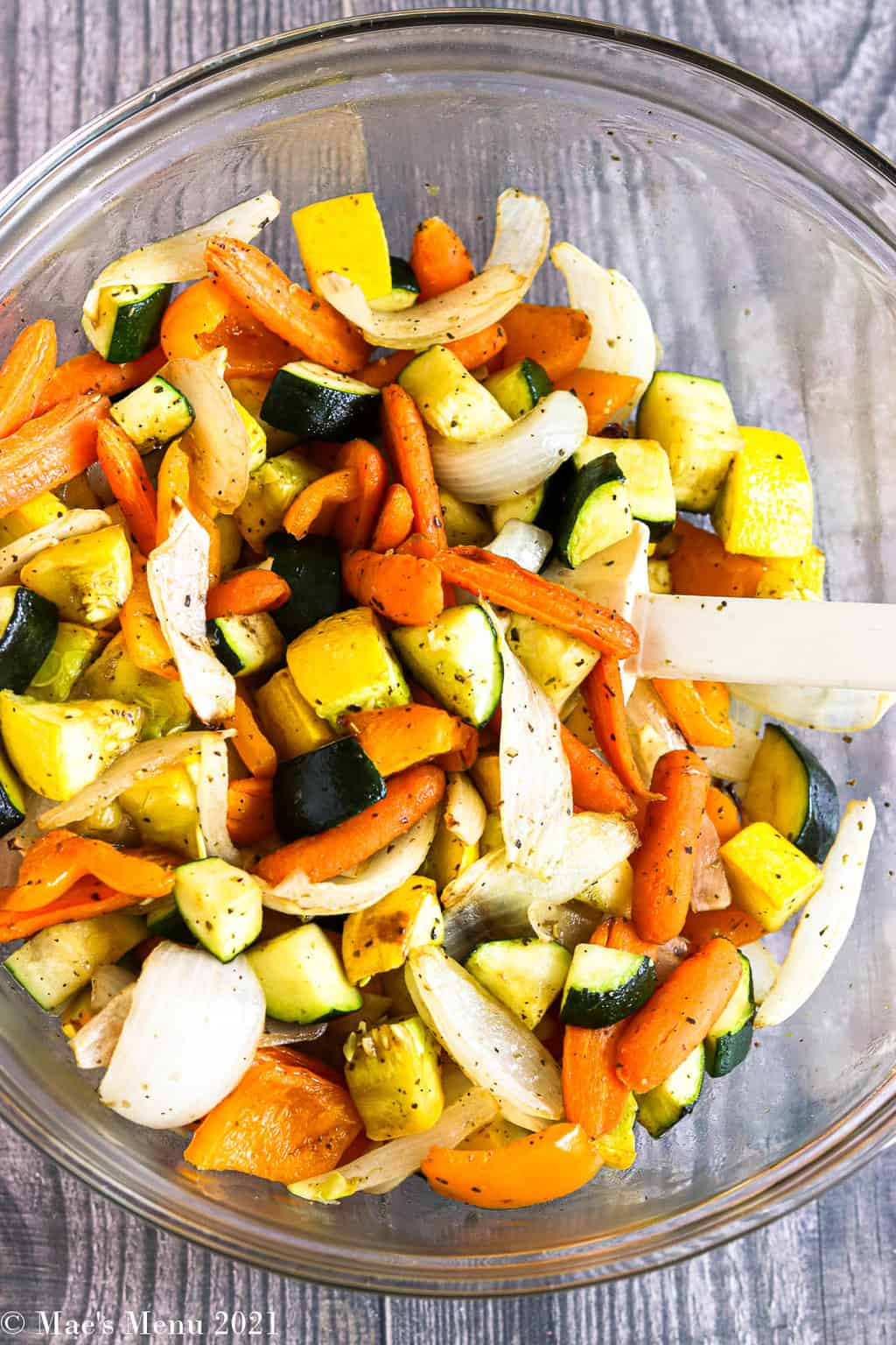 A large glass mixing bowl with air fryer roasted veggies in a spatula