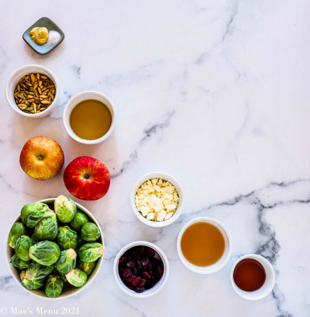 All of the ingredients for brussels sprouts slaw: brussels sprouts, apples, olive oil, pumpkin seeds, cranberries, mustard, salt, feta cheese, apple cider vinegar, and maple syrup