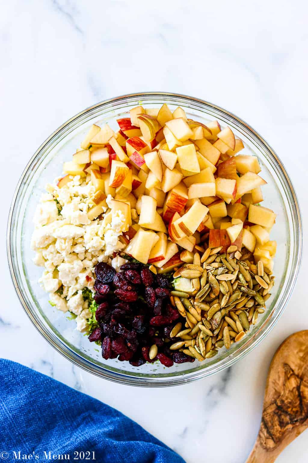 An overhead shot of a clear mixing bowl with apples, feta, pumpkin seeds, and cranberries