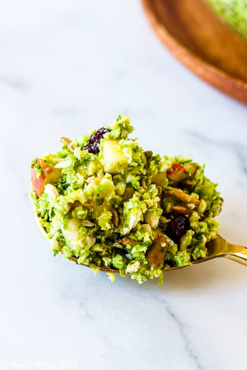 An up-close shot of a large serving spoon with brussels sprouts slaw