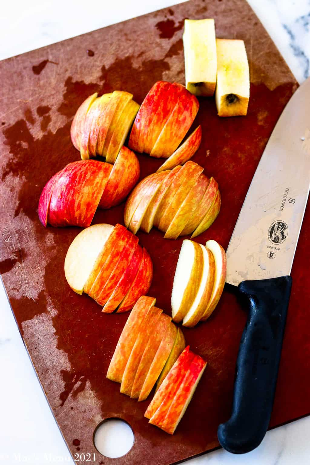 Sliced apples on a cutting board with a chef knife