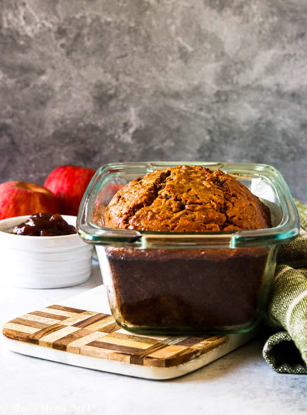 A side shot of a pan of a pan of healthy cinnamon apple bread with apples and apple butter in the background