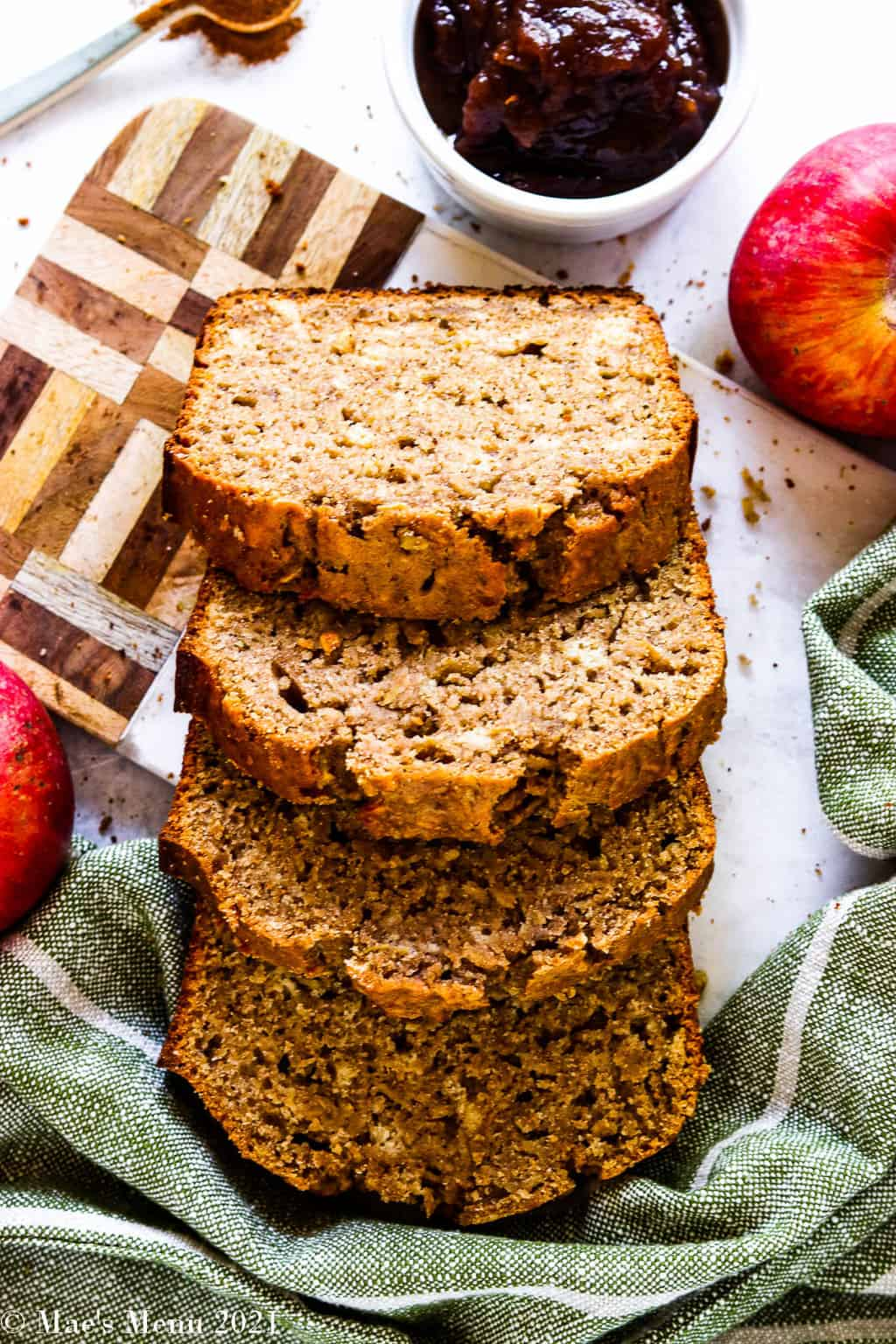 Slices of cinnamon apple bread resting on each other and off of a cutting board