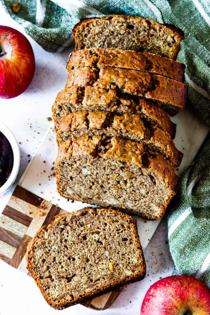 Healthy cinnamon apple bread sliced up and resting on a cutting board